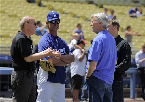 Los Angeles Dodgers owners Stan Kasten, left, Mark Walter, second from right, and Todd Boehly, right, talk with manager Don Mattingly, second from left, during batting practice before a baseball game against the St. Louis Cardinals, Saturday, May 25, 2013, in Los Angeles