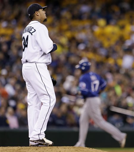 Seattle Mariners starting pitcher Felix Hernandez, left, looks toward the outfield as Texas Rangers' Nelson Cruz rounds the bases behind on a home run in the fifth inning of a baseball game Saturday, May 25, 2013, in Seattle