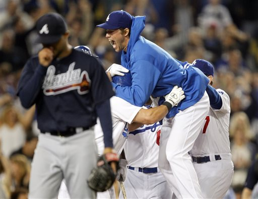 Los Angeles Dodgers' Clayton Kershaw, center, leaps on teammate Skip Schumaker after Schumaker scored the winning run on a wild pitch by Atlanta Braves relief pitcher Anthony Varvaro, left, in the tenth inning to win 2-1 during a baseball game Friday, June 7, 2013, in Los Angeles