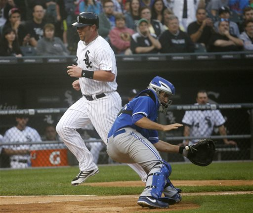 Chicago White Sox's Adam Dunn, left, scores past Toronto Blue Jays catcher Josh Thole, off a sacrifice fly by Hector Gimenez on a pitch from starting pitcher R.A. Dickey, during the second inning of a baseball game Monday, June 10, 2013, in Chicago