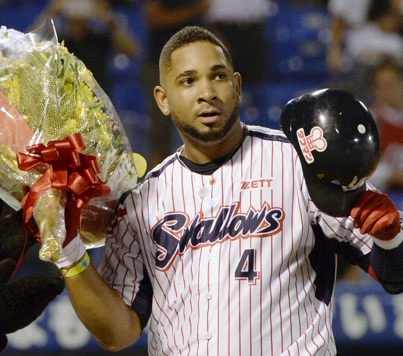Yakult Swallows' Wladimir Balentien holding a bouquet of flowers and his helmet celebrates with fans after hitting his 55th home run of the season in a regular season game against Hiroshima Carp at Jingu Stadium in Tokyo Wednesday, Sept. 11, 2013. Former major leaguer Balentien matched Japan record set by Sadaharu Oh in 1964 and equaled by ex-major leaguers Tuffy Rhodes in 2001 and Alex Cabrera in 2002