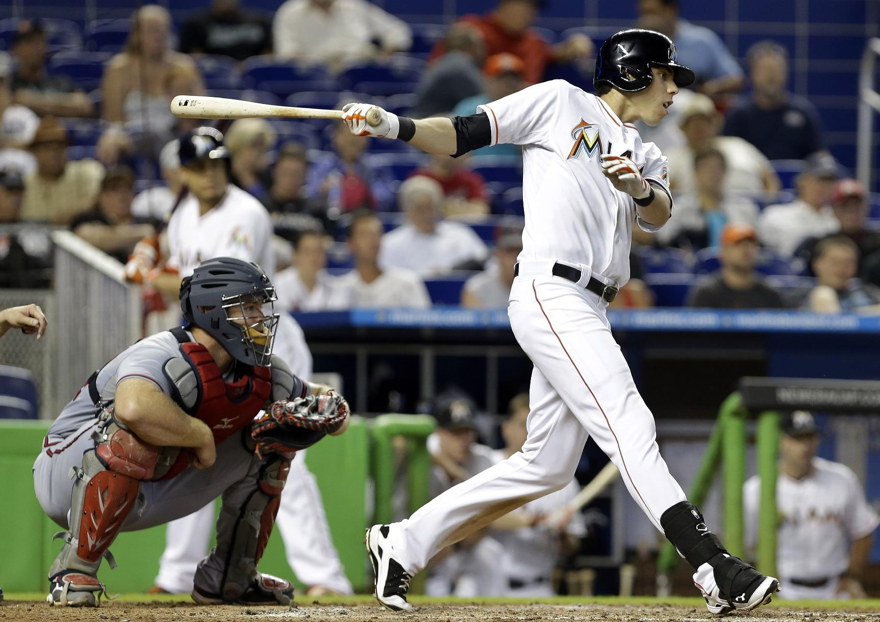Miami Marlins' Christian Yelich hits a single in the eighth inning as Atlanta Braves catcher Evan Gattis, right, looks on during a baseball game, Thursday, Sept. 12, 2013, in Miami