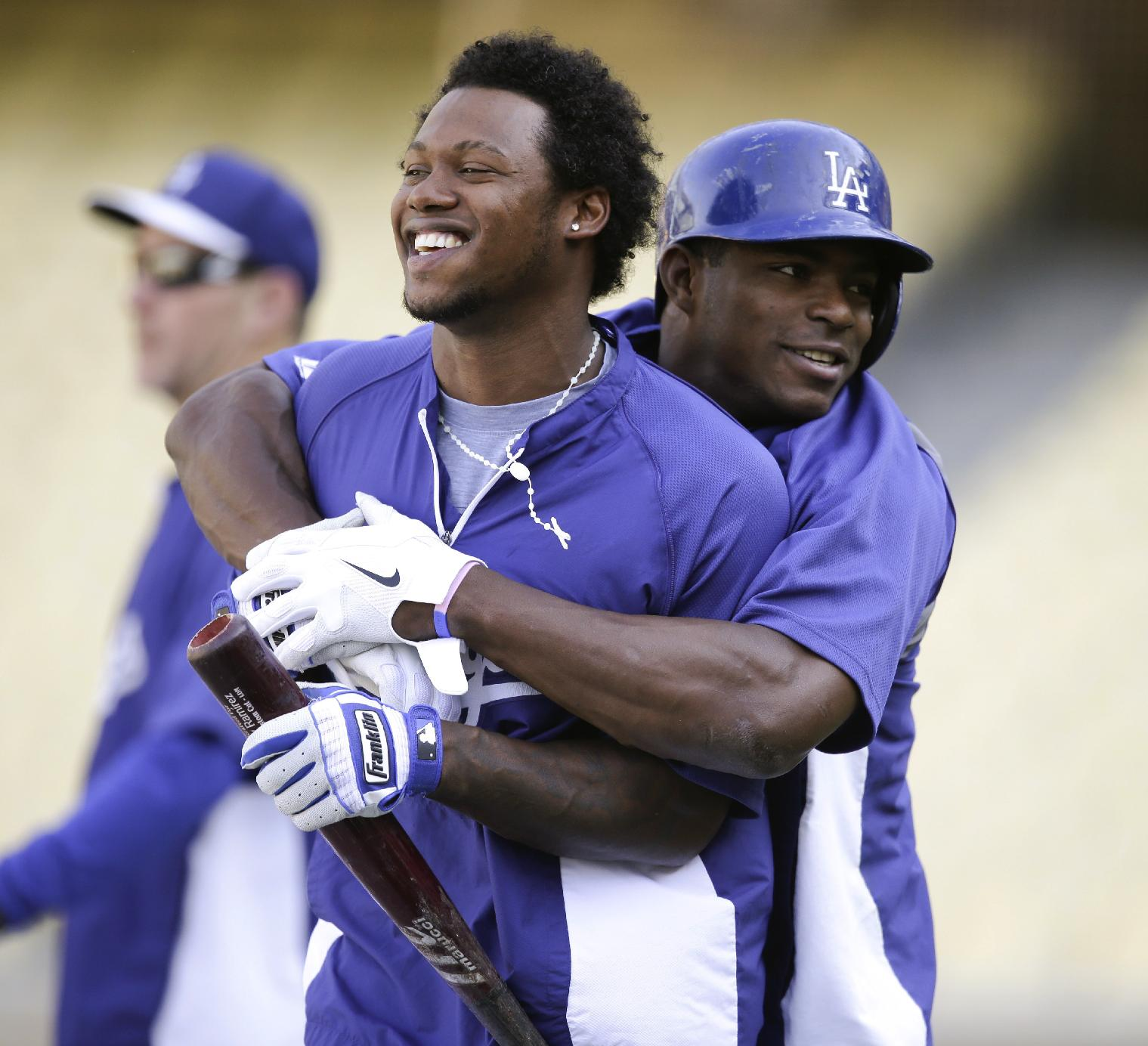 Los Angeles Dodgers' Yasiel Puig, right, jokes around with Hanley Ramirez during practice for a baseball game against the San Francisco Giants on Thursday, Sept. 12, 2013, in Los Angeles