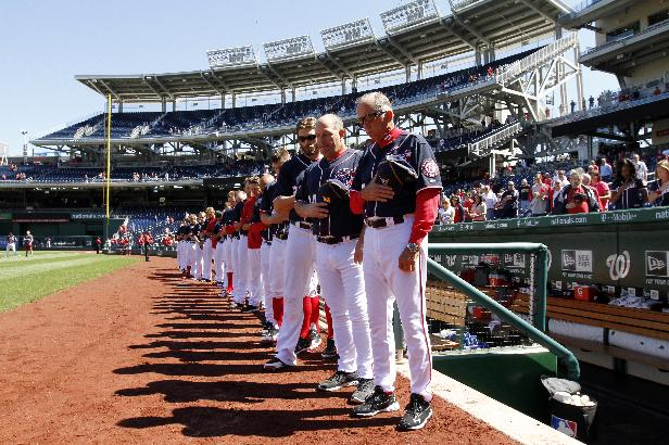 Holding Navy hats, Washington Nationals manager Davey Johnson, right, and others observe a moment of silence before a baseball game against the Atlanta Braves at Nationals Park Tuesday, Sept. 17, 2013, in Washington. The Nationals wore Navy hats, presented to them by Adm. James A. Winnefield, vice-chairman of the Joint Chiefs of Staff, before the game, to honor those killed and injured in the attack Monday at the nearby Washington Navy Yard