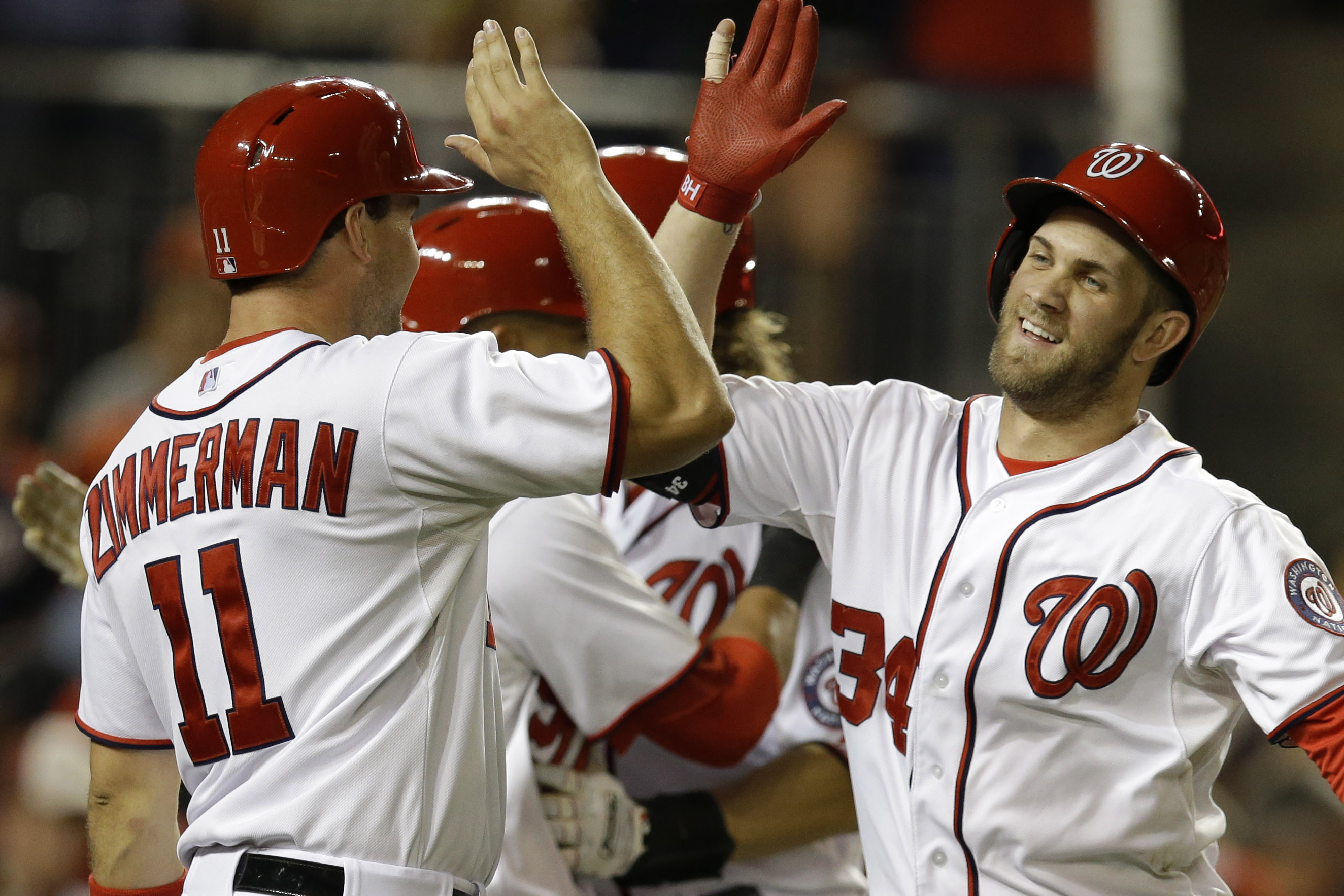 Washington Nationals' Bryce Harper (34) high-fives teammate Ryan Zimmerman (11) after scoring with a three-run home run against the Miami Marlins during the first inning of a baseball game at Nationals Park in Washington, Thursday, Sept. 19, 2013. Nationals' Ryan Zimmerman and Jayson Werth also scored on the play