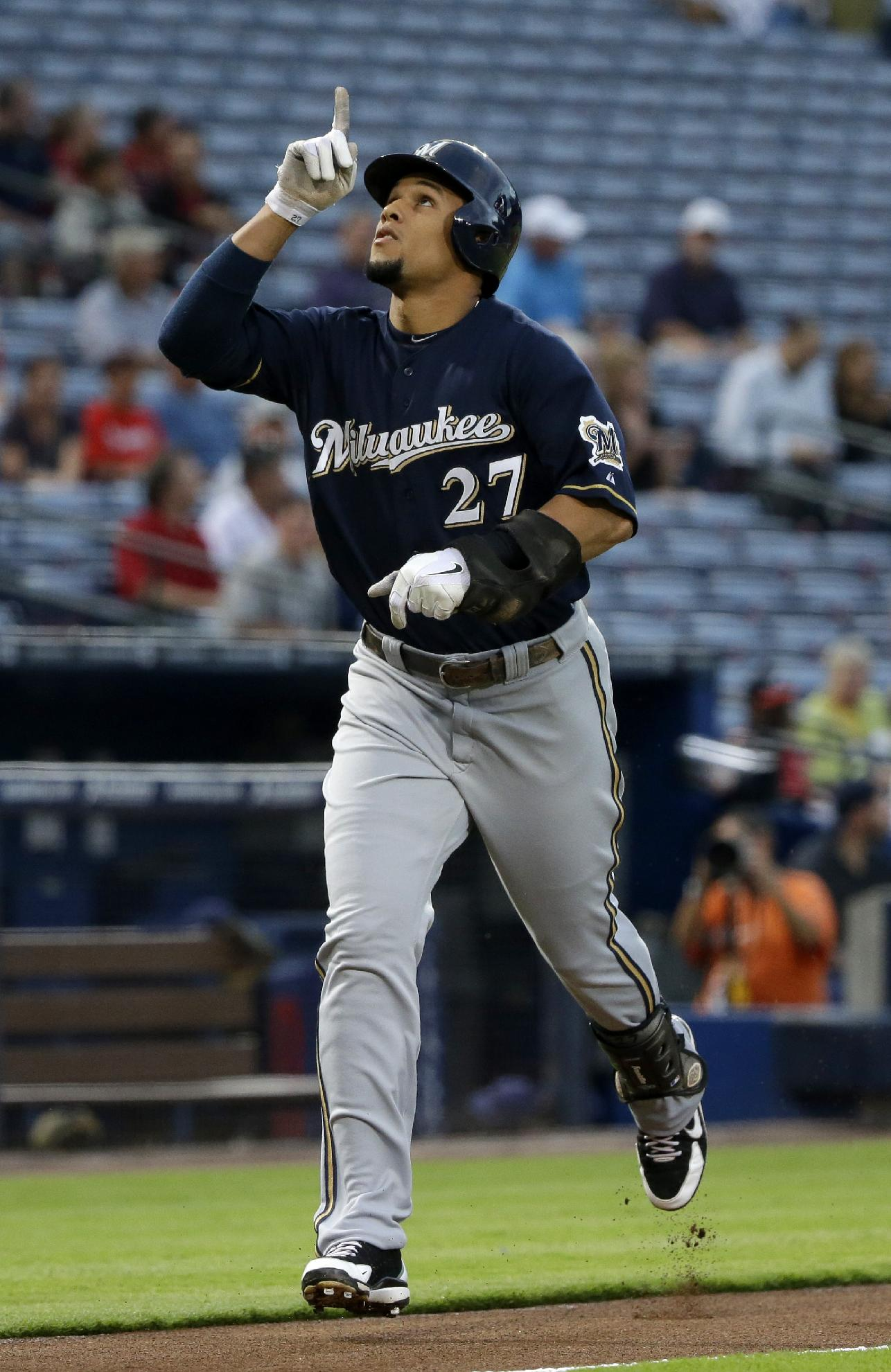 Milwaukee Brewers' Carlos Gomez points to the sky as he runs to home plate after hitting a home run in the first inning of a baseball game against the Atlanta Braves, Monday, Sept. 23, 2013, in Atlanta