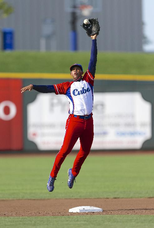 In this July 19, 2013 file photo, Cuba second baseman Jose Miguel Fernandez warms up before the start of an exhibition baseball game against the United States in Papillion, Neb. One of the five top active players in Cuba's National Series, Fernandez led the league in hitting last season with a .393 batting average. Cuba on Friday, Sept. 27, 2013 announced that athletes from all sports will soon be able to ply their trade in foreign leagues