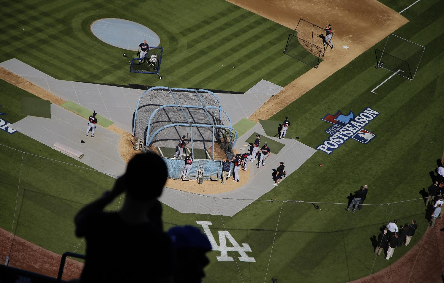 A fan is silhouetted as the Atlanta Braves take batting practice before Game 3 of the National League division baseball series against the Los Angeles Dodgers, Sunday, Oct. 6, 2013, in Los Angeles