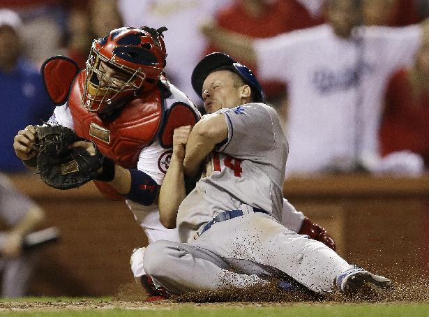 St. Louis Cardinals catcher Yadier Molina tags out Los Angeles Dodgers' Mark Ellis at home during the 10th inning of Game 1 of the National League baseball championship series Friday, Oct. 11, 2013, in St. Louis