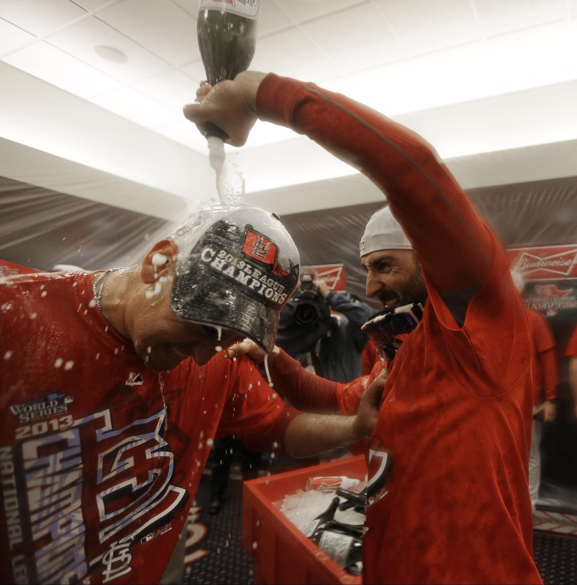 CORRECTS SPELLING OF ALLEN CRAIG FROM ALAN AS ORIGINALLY SENT- St. Louis Cardinals' Allen Craig has Champagne poured on him by teammate Daniel Descalso after Game 6 of the National League baseball championship series against the Los Angeles Dodgers, Friday, Oct. 18, 2013, in St. Louis. The Cardinals won 9-0 to win the series