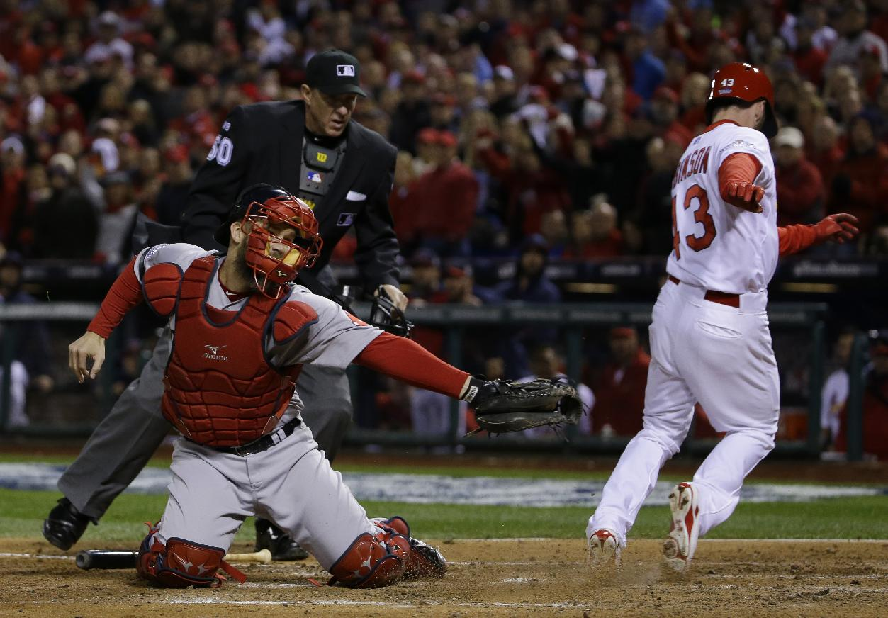 Home plate umpire Paul Emmel watches as St. Louis Cardinals right fielder Shane Robinson scores past Boston Red Sox catcher David Ross on an RBI single by Matt Carpenter during the seventh inning of Game 4 of baseball's World Series Sunday, Oct. 27, 2013, in St. Louis