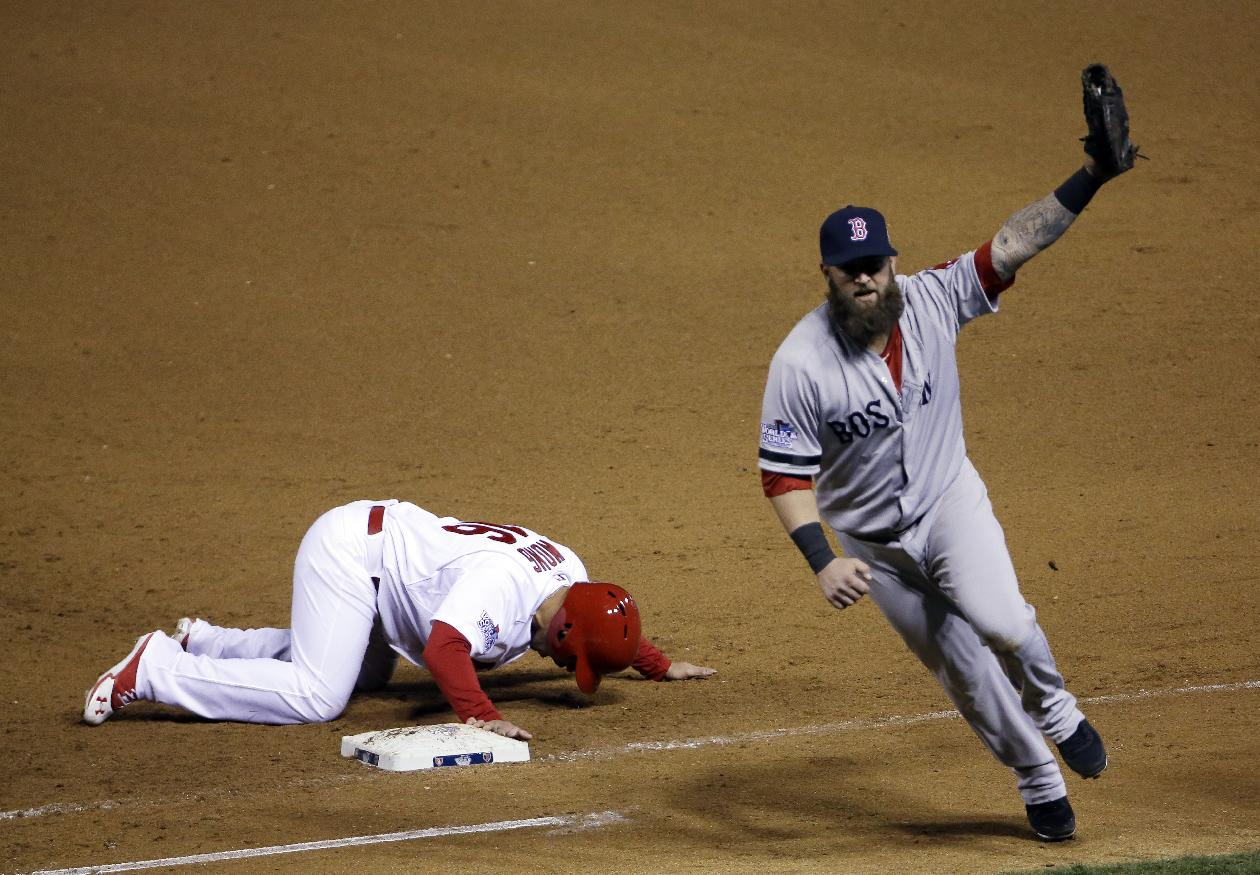 Boston Red Sox first baseman Mike Napoli celebrates after tagging out St. Louis Cardinals' Kolten Wong on a pick-off attempt to end Game 4 of baseball's World Series Sunday, Oct. 27, 2013, in St. Louis. The Red Sox won 4-2 to ties the series at 2-2