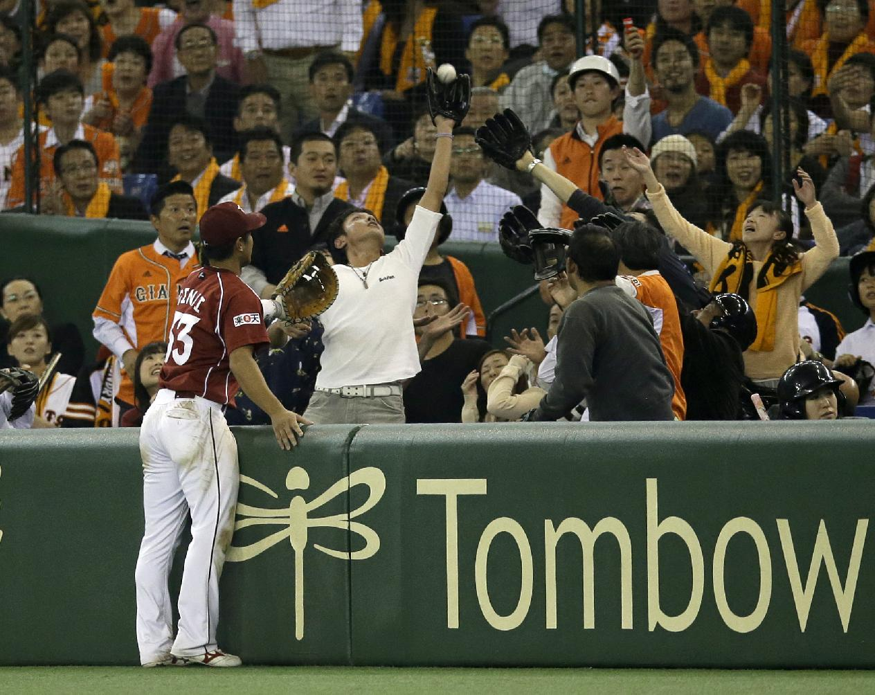 Rakuten Eagles first baseman Ginji Akaminai looks at a fan catch a foul fly in the 10th inning of Game 5 of baseball's Japan Series against the Yomiuri Giants at Tokyo Dome in Tokyo, Thursday, Oct. 31, 2013