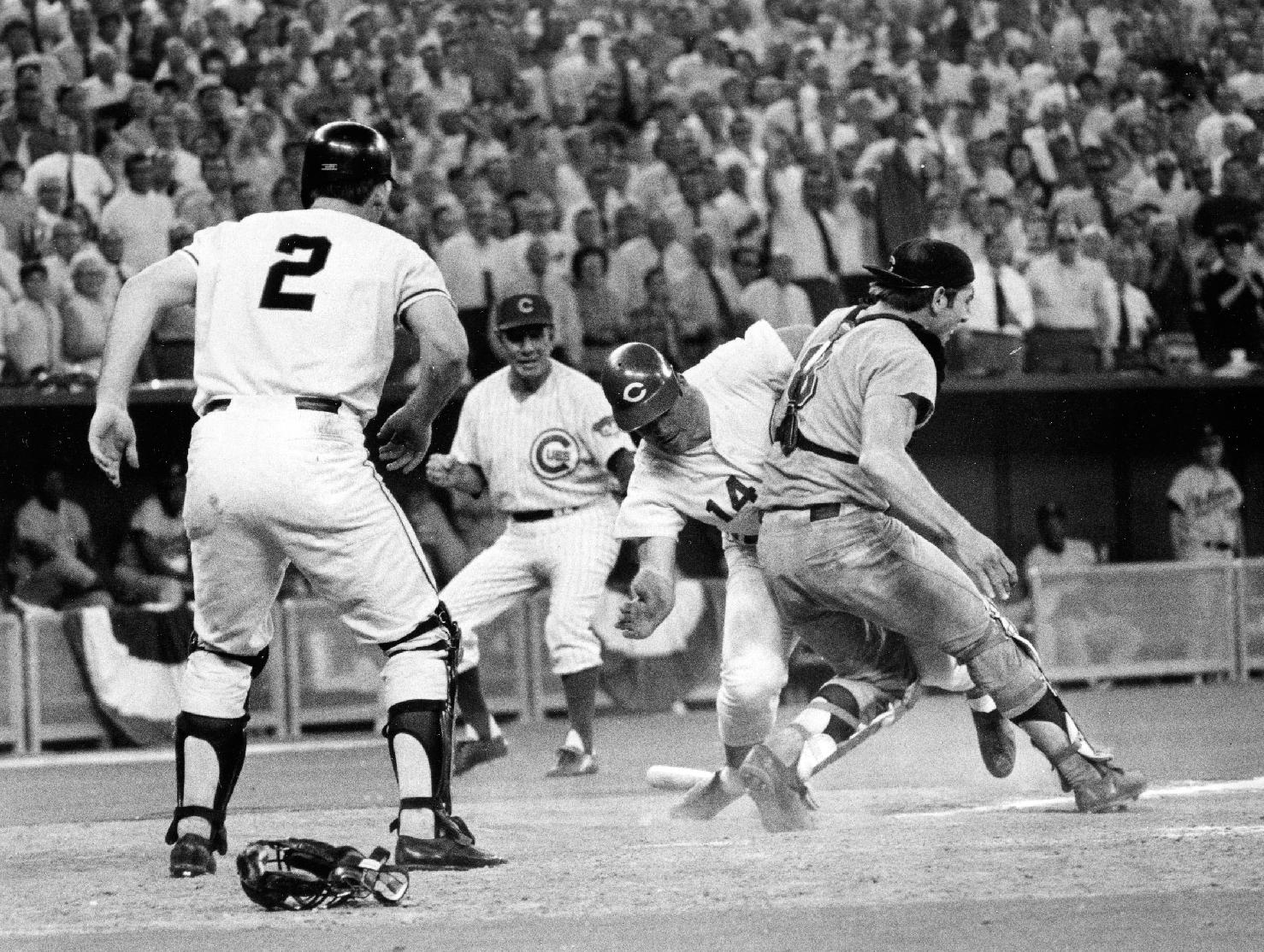 In this July 14, 1970 file photo, Cincinnati Reds' Pete Rose (14) slams into Cleveland Indians' catcher Ray Fosse to score a controversial game-winning run for the National League team in the 12th inning of the 1970 All-Star game in Cincinnati. Fosse suffered a fractured shoulder in the collision. Looking on are the Reds' third base coach Leo Durocher, and Cincinnati Reds' next hitter Dick Dietz (2). Major League Baseball plans to eliminate home plate collisions, possibly as soon as next season but no later than by 2015. New York Mets general manager Sandy Alderson, chairman of the rules committee, made the announcement Wednesday, Dec. 11, 2013 at the winter meetings. Player safety and concern over concussions were major factors in the decision
