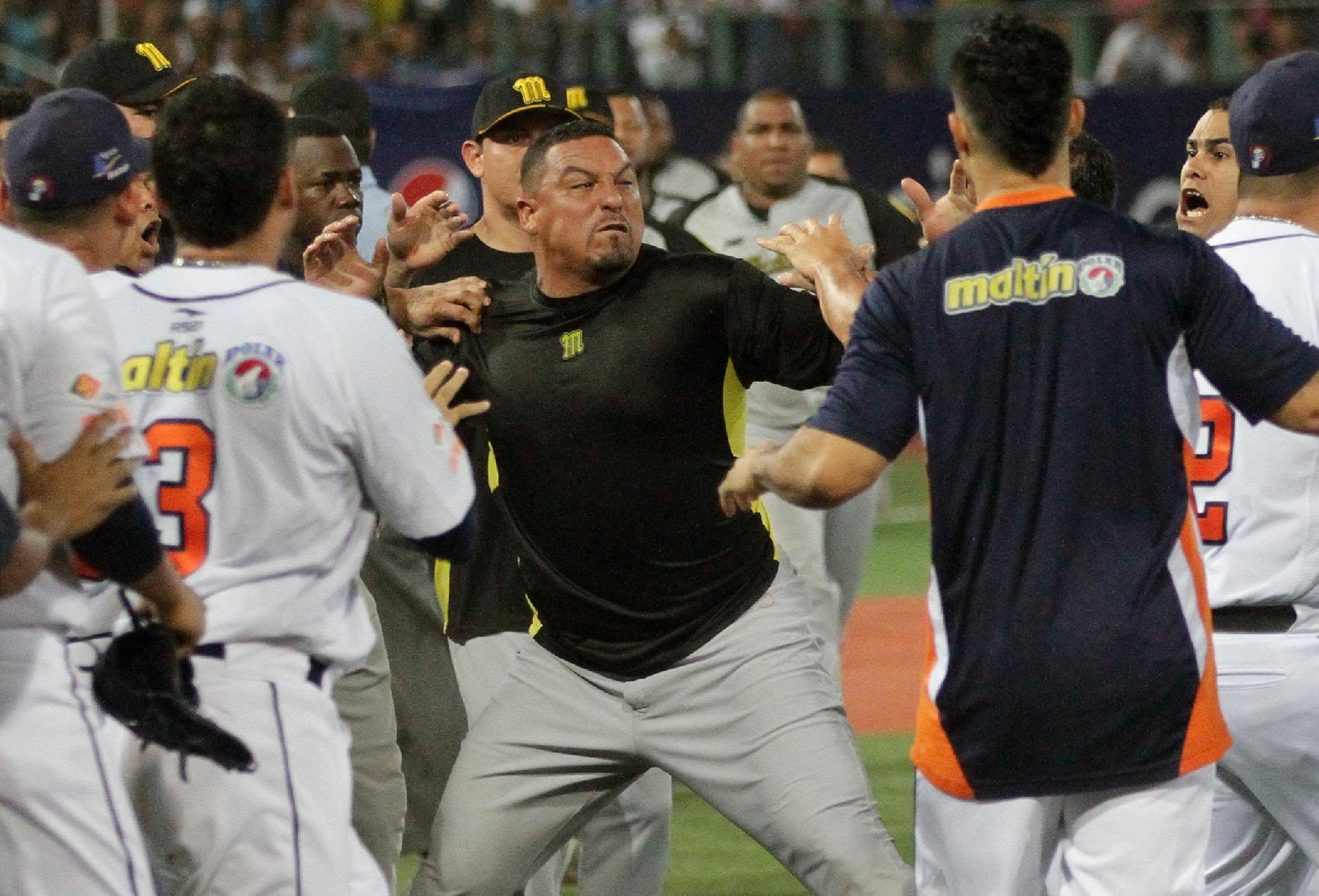 In this photo taken on Saturday, Jan 25, 2014. Venezuela former major league pitcher Carlos Zambrano, center, gestures during a brawl at the third game of the Venezuelan Baseball championship final playoff between Magallanes from Valencia and Caribes from Puerto La Cruz, in Puerto La Cruz ,Venezuela. Zambrano struck pitcher Mayckol Guiape of the rival Caribes de Anzoategui after teammate Ezequiel Carrera of the Navegantes del Magallanes was hit by a pitch.(AP Photo /Elyxandro Cegarra)