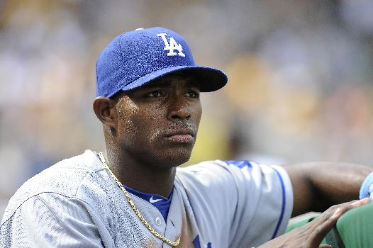 In this June 16, 2013, file photo, Los Angeles Dodgers right fielder Yasiel Puig watches from the in the dugout during the fourth inning of a baseball game against the Pittsburgh Pirates in Pittsburgh. The Florida Highway Patrol says that Puig has been arrested and charged with reckless driving on Saturday, Dec. 28, 2013, after officers clocked him driving 110 mph in a 70 mph zone