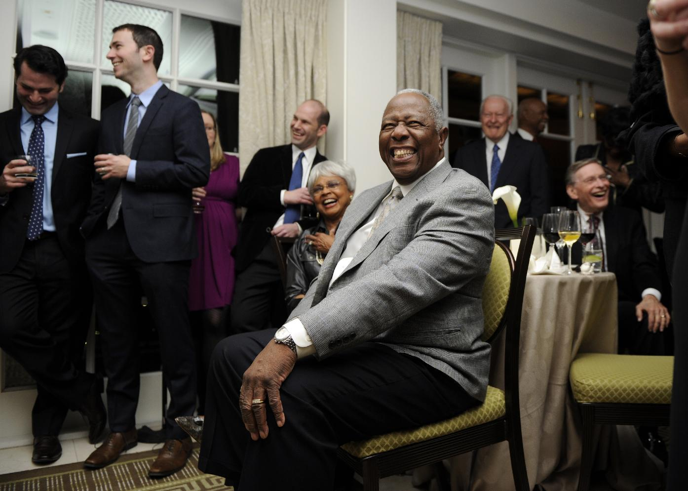 Baseball Hall of Famer Hank Aaron, center, smiles during a reception in his honor, Friday, Feb. 7, 2014, in Washington. Aaron turned 80 this week and is being celebrated with a series of events in Washington