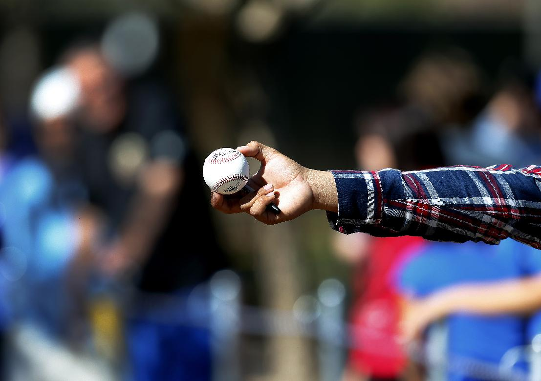 A fan holds out a ball for an autograph during Los Angeles Dodgers spring training baseball practice Sunday, Feb. 9, 2014, in Glendale, Ariz