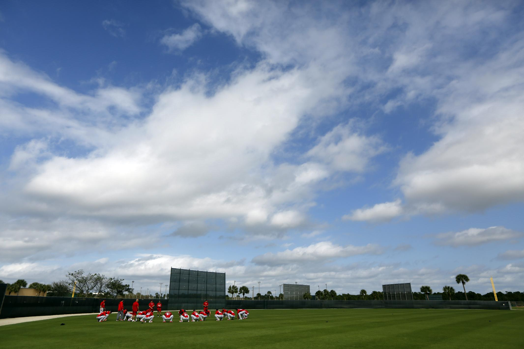 Members of the St. Louis Cardinals warm up at the start of the first official spring training baseball practice for the team's pitchers and catchers Thursday, Feb. 13, 2014, in Jupiter, Fla