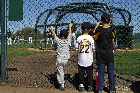 James, Andrew, and William Baird, of Naples, Fla., watch a bunting drill for pitchers at Pittsburgh Pirates baseball spring training in Bradenton, Fla., Sunday, Feb. 16, 2014