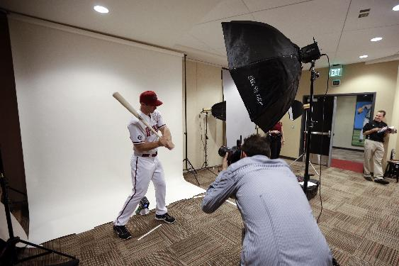 Photographer Mark Rebilas, center, takes a portrait picture of Arizona Diamondbacks first baseman Paul Goldschmidt during the team's photo day before a spring training baseball workout, Wednesday, Feb. 19, 2014, in Scottsdale, Ariz