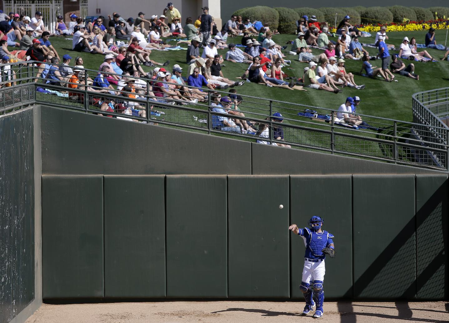 Some of the more than 9,000 fans in attendance watch from the center-field lawn as a Kansas City Royals catcher warms up in the bullpen in the fourth inning of an exhibition baseball game between the Royals and the Texas Rangers, Thursday, Feb. 27, 2014, in Surprise, Ariz