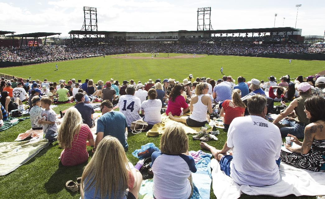 Fans watch from the outfield grass as the Arizona Diamondbacks and the Chicago Cubs compete during a spring training baseball game on Thursday, Feb. 27, 2014, in Mesa, Ariz
