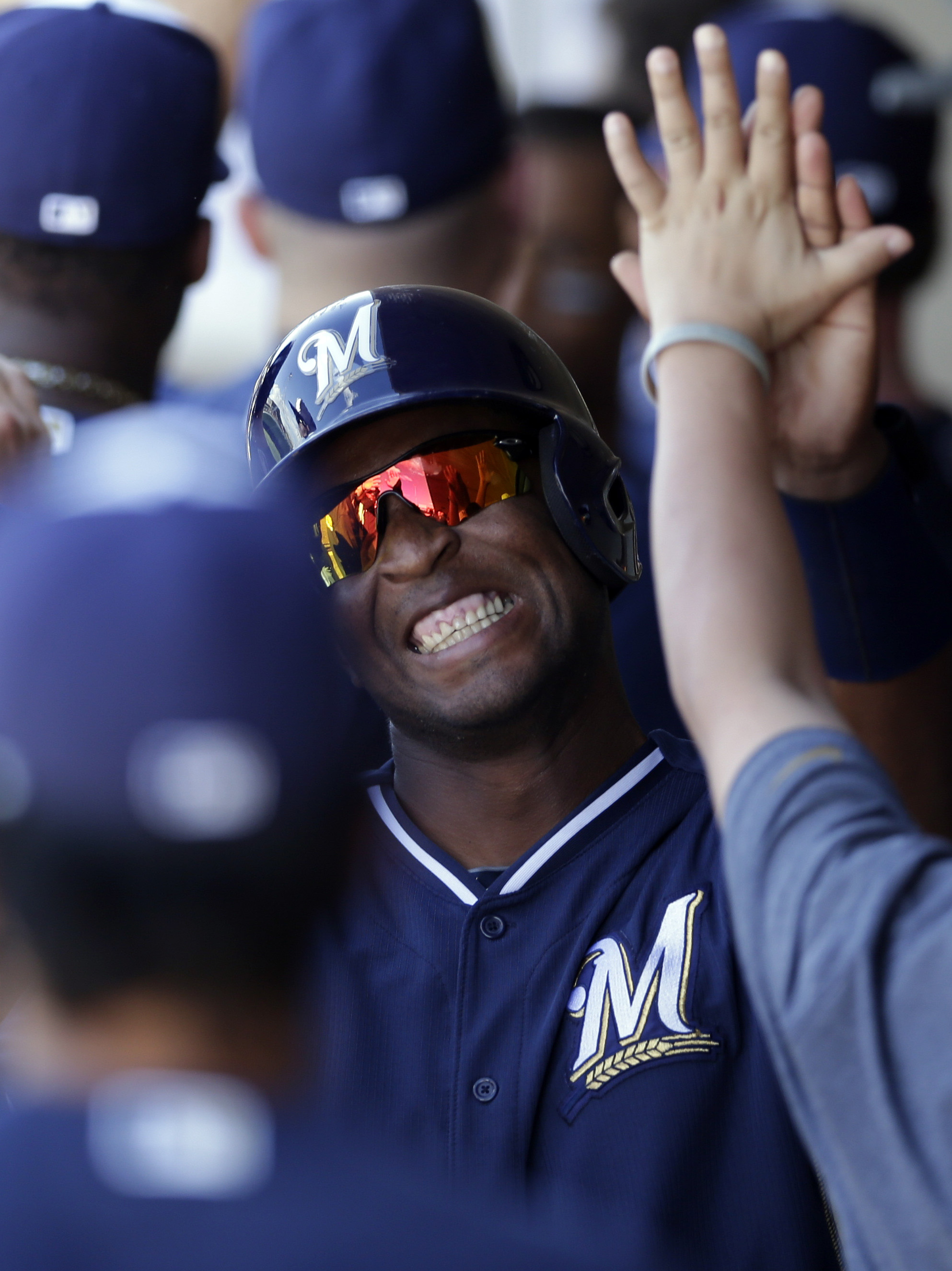 Milwaukee Brewers' Robinzon Diaz smiles as he is greeted by teammates after scoring off a single hit by Juan Francisco while playing against the Oakland Athletics during the fifth inning of a spring training baseball game on Thursday, Feb. 27, 2014, in Scottsdale, Ariz
