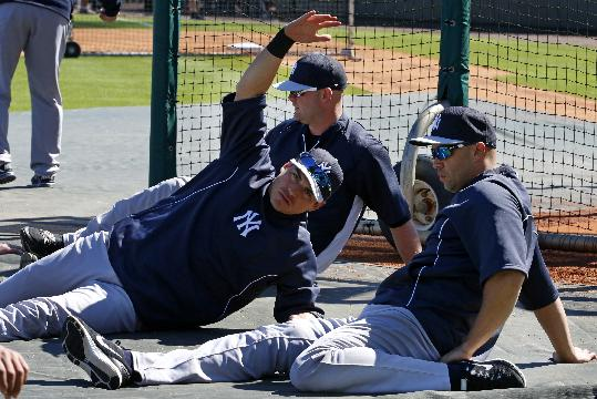 New York Yankees' Jacoby Ellsbury, center, Brian McCann, rear, and Carlos Beltran stretch before an exhibition spring training baseball game against the Detroit Tigers in Lakeland, Fla.,  Friday, Feb. 28, 2014