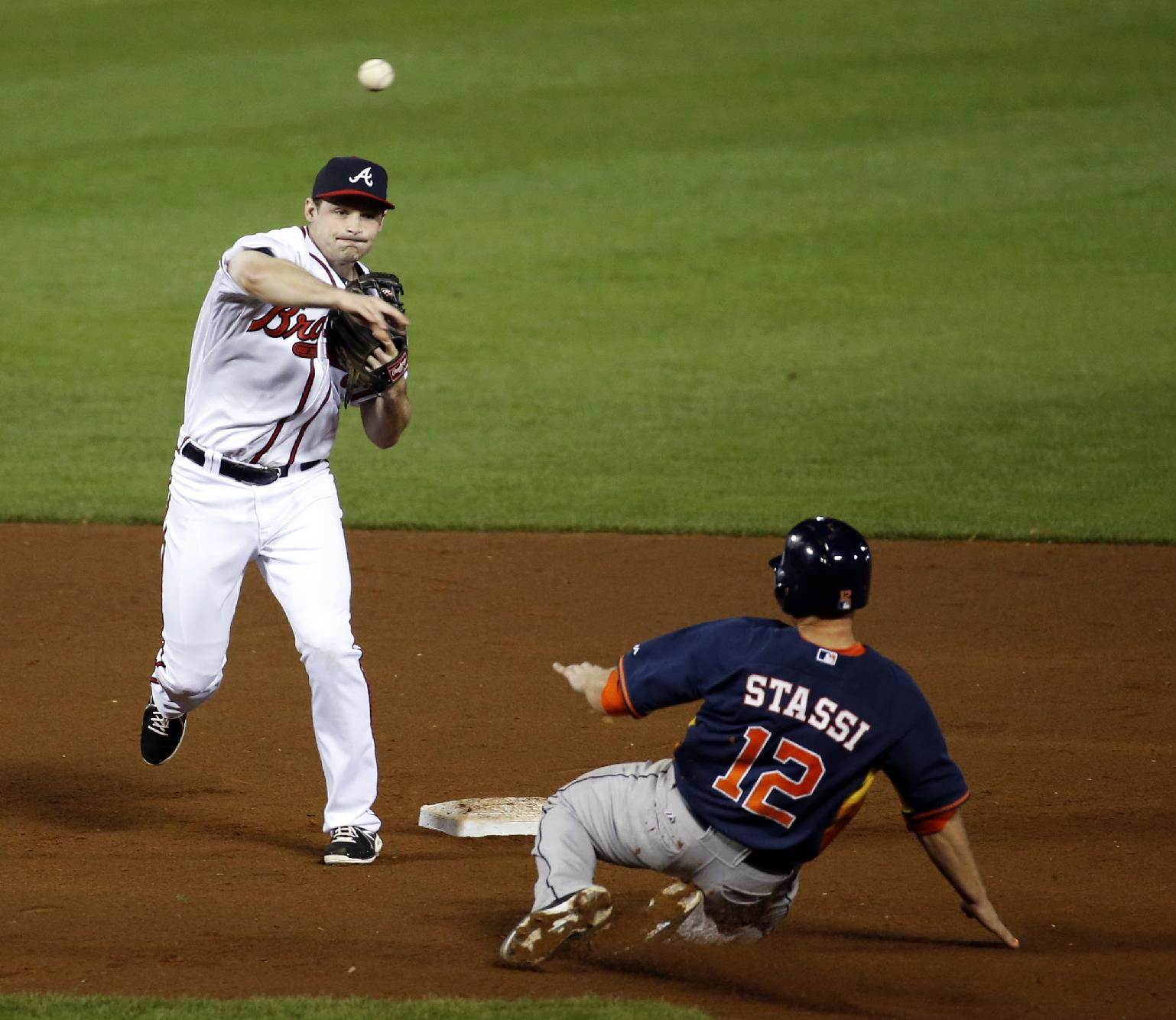 Houston Astros catcher Max Stassi is out at second, as Atlanta Braves second baseman Phil Gosselin makes the throw to first to complete a double play in the eighth inning of an exhibition baseball game, Friday, Feb. 28, 2014, in Kissimmee, Fla. The Astros won 7-5