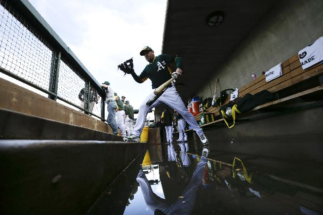 Oakland Athletics third baseman Nick Punto leaps over water on the floor of the dugout after a rain delay before facing the Texas Rangers in a spring training baseball game Saturday, March 1, 2014, in Phoenix
