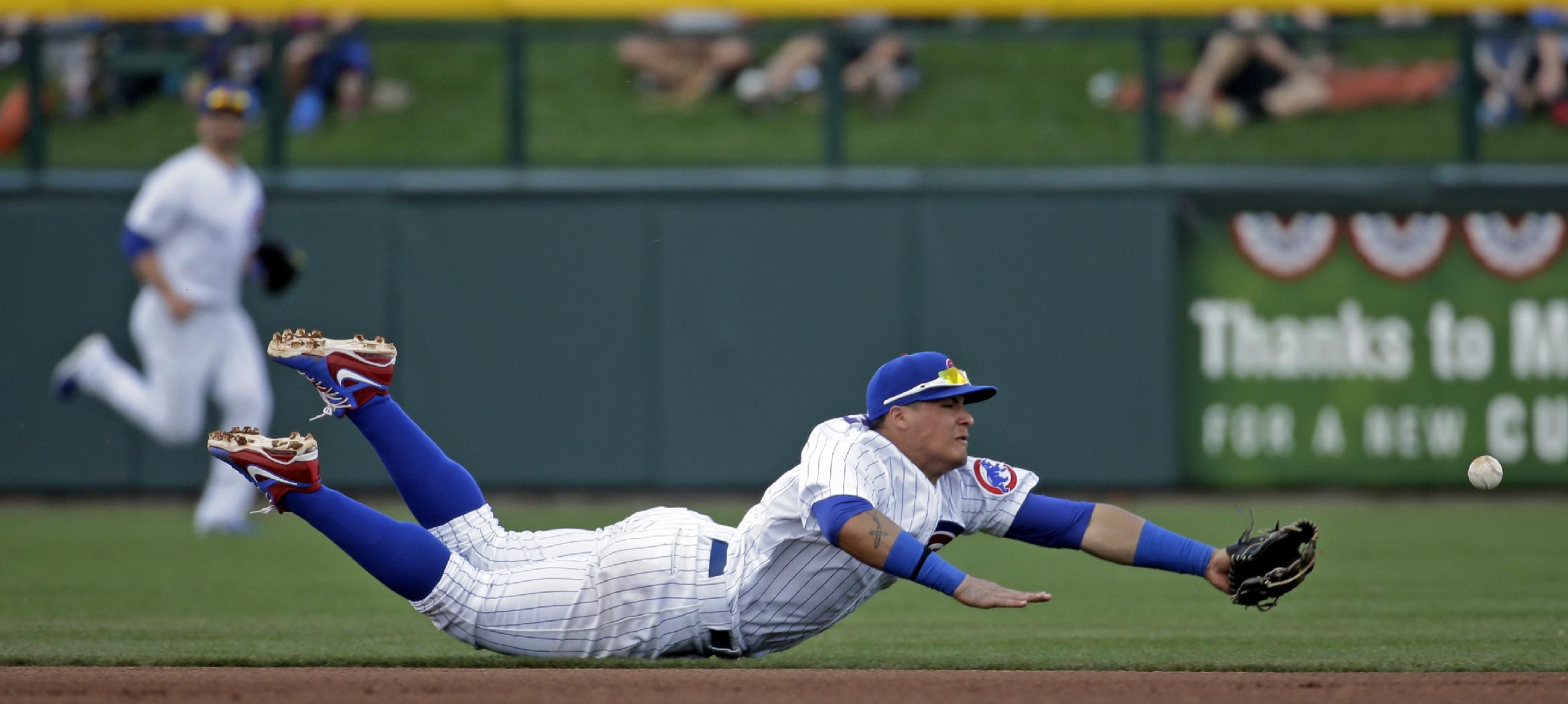 Chicago Cubs' Javier Baez can't come up with a ball hit by Kansas City Royals' Lorenzo Cain during the fourth inning of an exhibition spring training baseball game, Sunday, March 2, 2014, in Mesa, Ariz