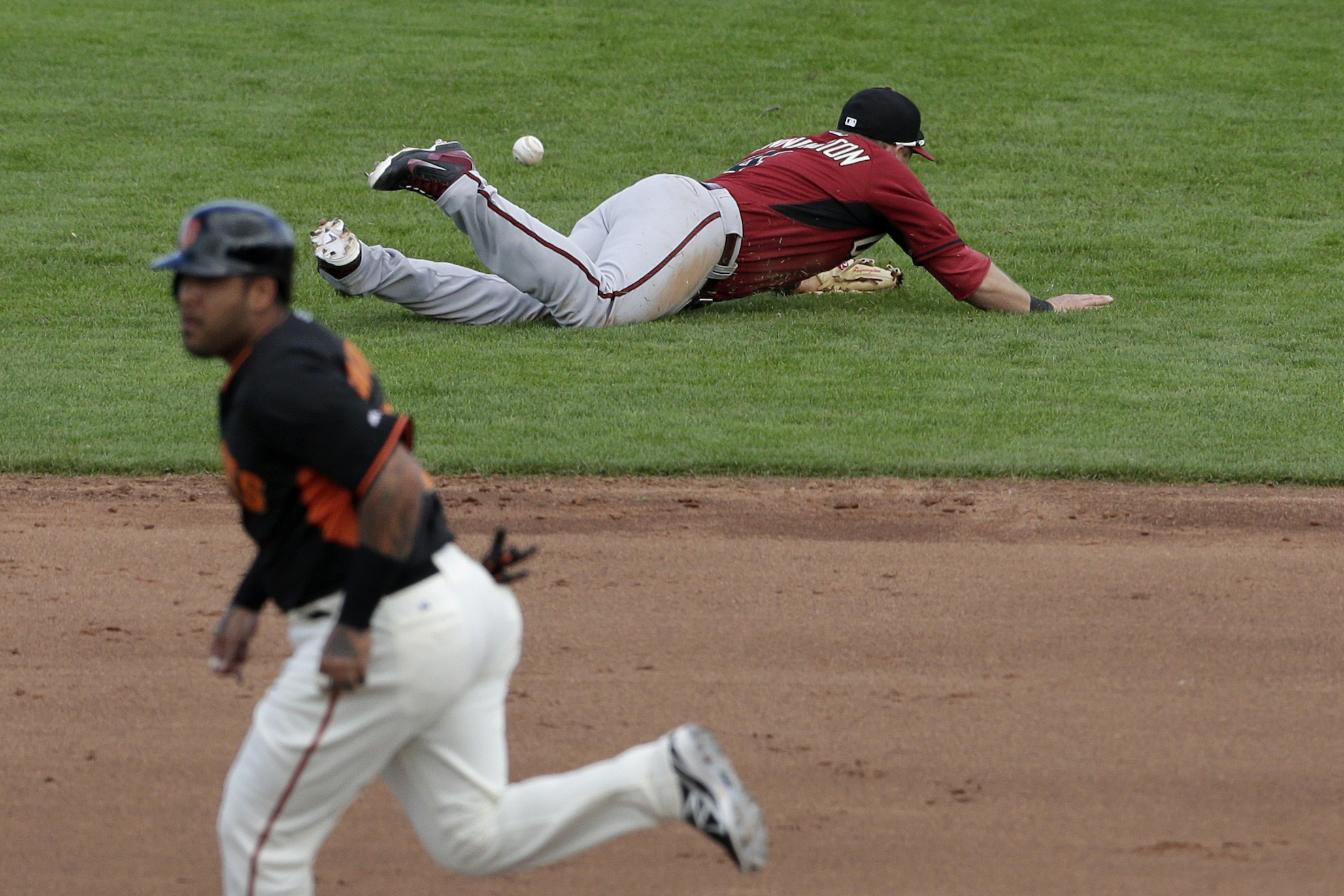 Arizona Diamondbacks shortstop Cliff Pennington, can't reach a hit for a single by San Francisco Giants' Joaquin Arias as the Giants' Hector Sanchez, below, makes his way to second base during the fifth inning of a spring training baseball game Sunday, March 2, 2014, in Scottsdale, Ariz