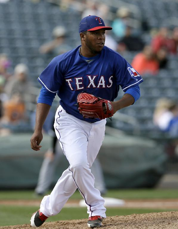 Texas Rangers pitcher Neftali Feliz watches the hit by Chicago White Sox's Conor Gillaspie in the sixth inning of a spring exhibition baseball game on Sunday, March 2, 2014, in Surprise, Ariz