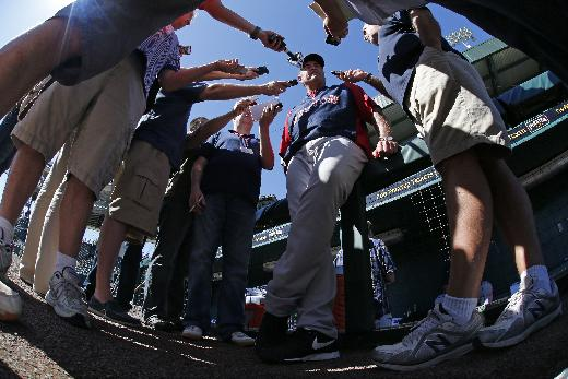In this image shot with a fisheye lense, Boston Red Sox manager John Farrell, center, talks with reporters before an exhibition spring training baseball game against the Pittsburgh Pirates in Bradenton, Fla., Monday, March 3, 2014