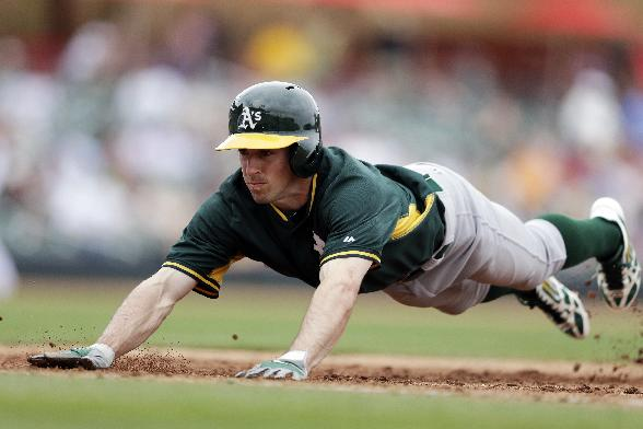 Oakland Athletics' Billy Burns dives back safely to first base while pinch running for Nick Punto during the sixth inning of an exhibition spring training baseball game against the Arizona Diamondbacks, Thursday, March 6, 2014, in Scottsdale, Ariz