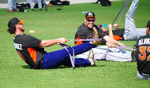 Miami Marlins catcher Jarrod Saltalamacchia, left, raided teammate Jose Fernandez's, right, locker and decided to wear Fernandez's jersey, purple jeans and gold high top sneakers to the Marlins morning stretch during a spring training baseball workout, Friday, March 7, 2014, in Jupiter, Fla