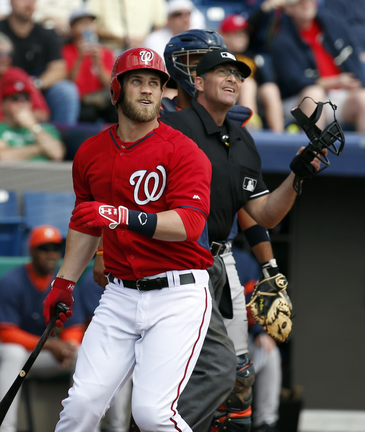 Washington Nationals' Bryce Harper, left, watches his two-run homer with home plate umpire Paul Nauert in the first inning of a spring exhibition baseball game against the Houston Astros, Friday, March 7, 2014, in Viera, Fla