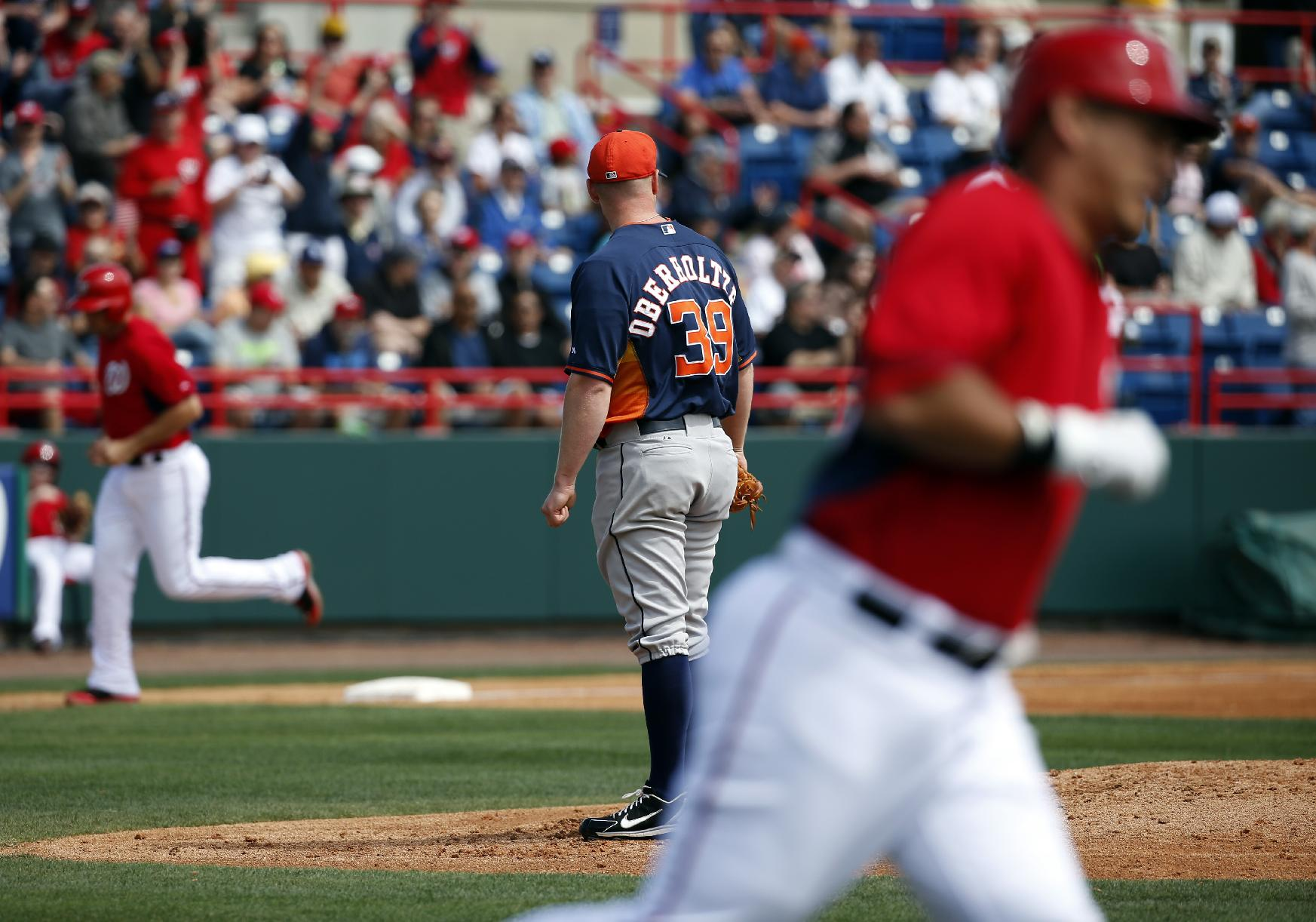 Houston Astros starting pitcher Brett Oberholtzer (39) watches as members of the Washington Nationals round the bases during Wilson Ramos' three-run homer in the first inning of a spring exhibition baseball game, Friday, March 7, 2014, in Viera, Fla