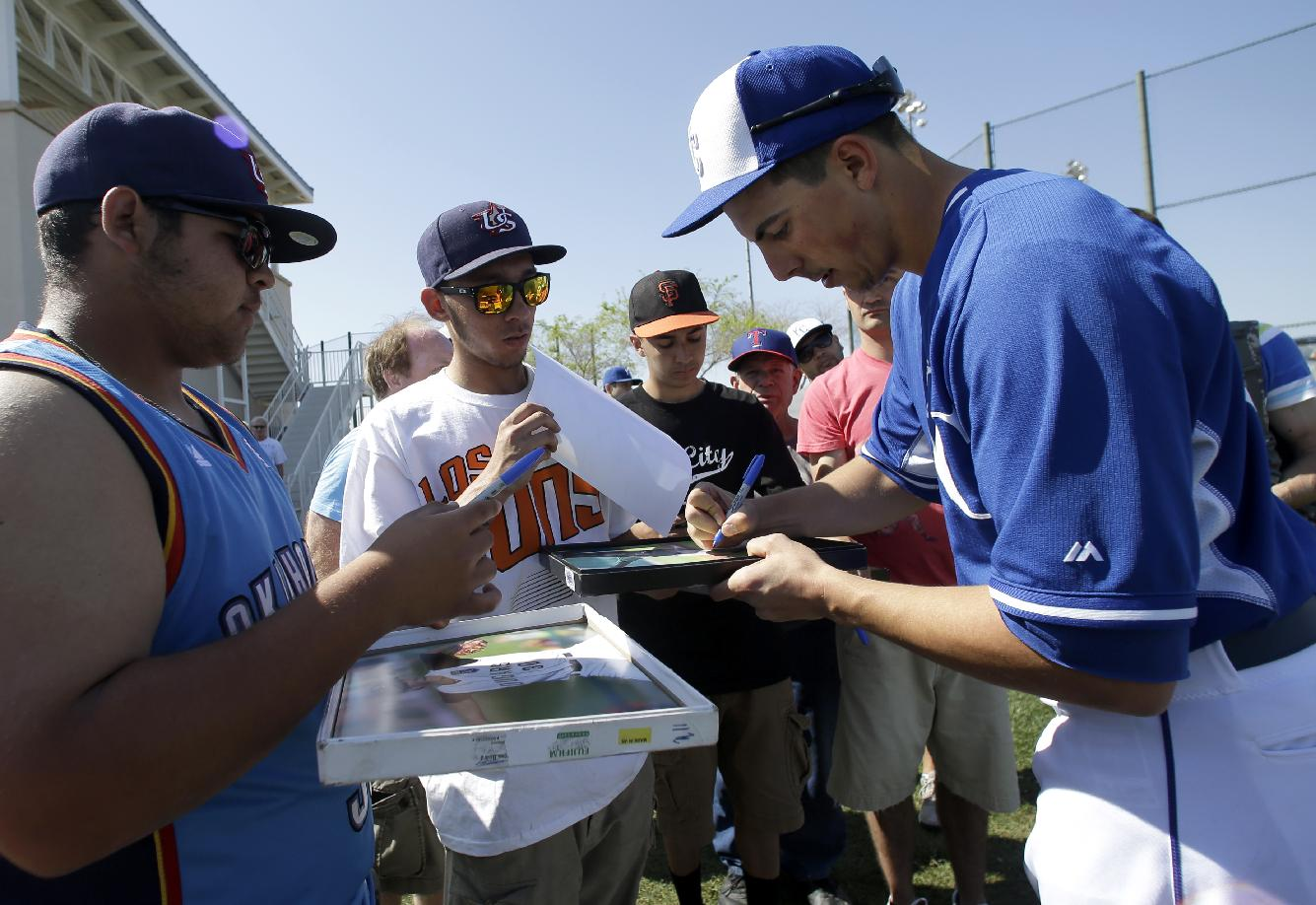 Kansas City Royals' Kyle Zimmer signs autographs for fans after a morning workout during spring baseball practice, Friday, March 7, 2014, in Surprise, Ariz
