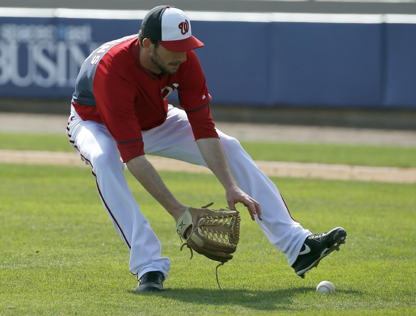 Washington Nationals relief pitcher Jerry Blevins grabs a ball hit by Houston Astros Jonathan Villar, who was out at first on the play, in the sixth inning of a spring exhibition baseball game, Friday, March 7, 2014, in Viera, Fla. The Nationals won 8-5