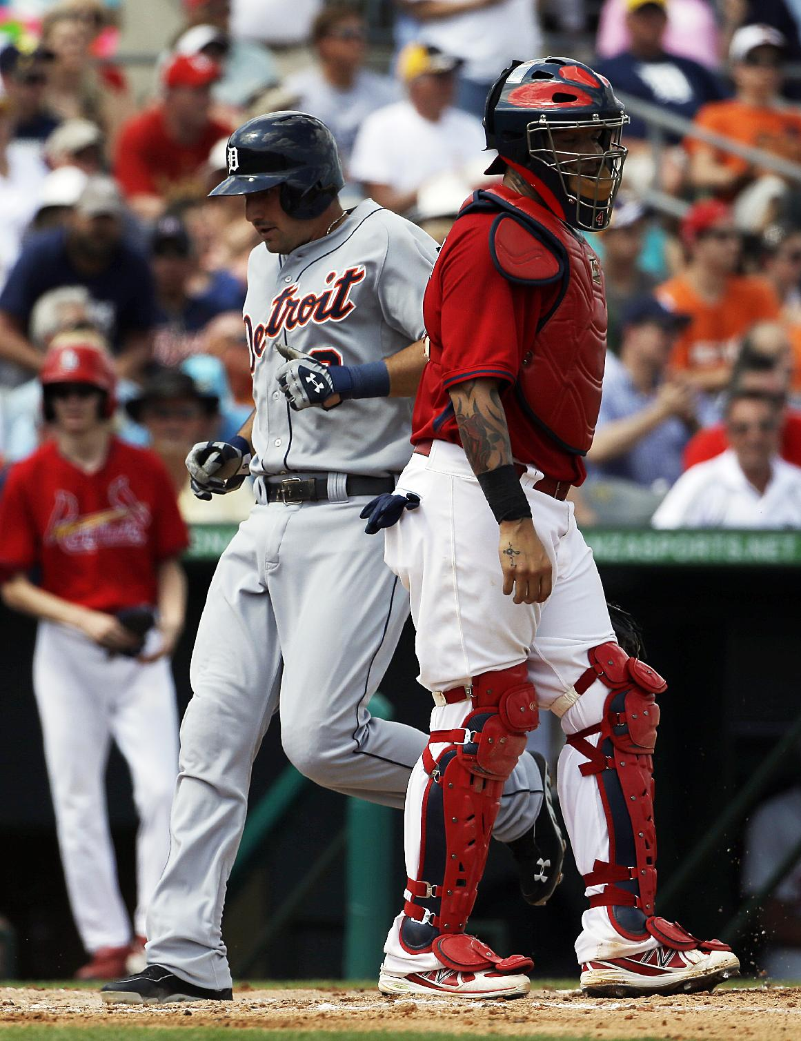 Detroit Tigers' Nick Castellanos, left scores off a triple by teammate Steven Moya as St. Louis Cardinals catcher Yadier Molina, right, looks on in the third inning of an exhibition spring training baseball game, Monday, March 10, 2014, in Jupiter, Fla