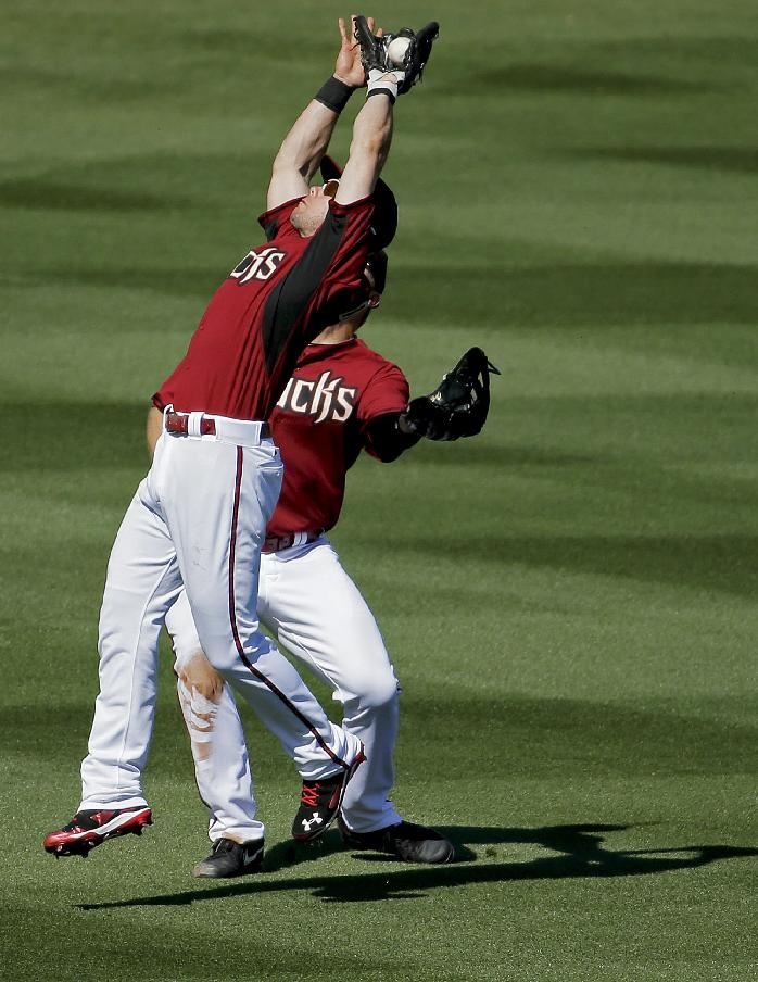 Arizona Diamondbacks left fielder Matt Tuiasosopo, left, nearly collides with left fielder Shelley Duncan catching a fly ball hit by Cleveland Indians's Yan Gomes during the fifth inning of a spring exhibition baseball game in Scottsdale, Ariz., Tuesday, March 11, 2014