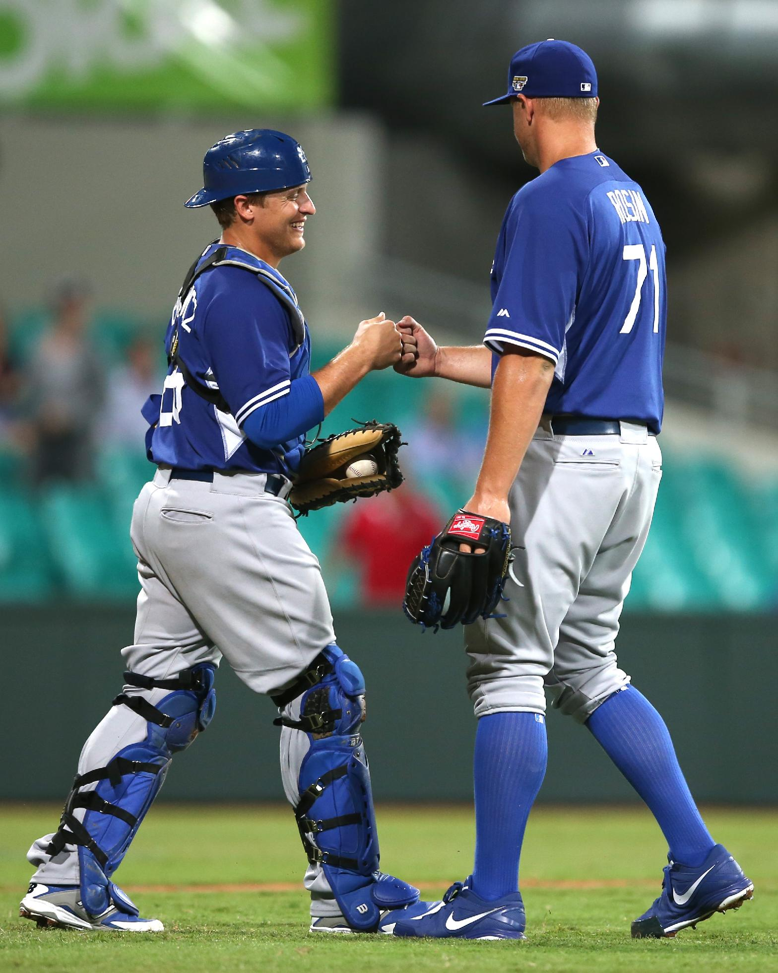 The Los Angles Dodgers' Tim Federowicz, left, and his teammate Seth Rosin, right, congratulate each other after their win in an exhibition baseball game against Team Australia at the Sydney Cricket ground in Sydney, Thursday, March 20, 2014. The Dodgers won the game 4-2