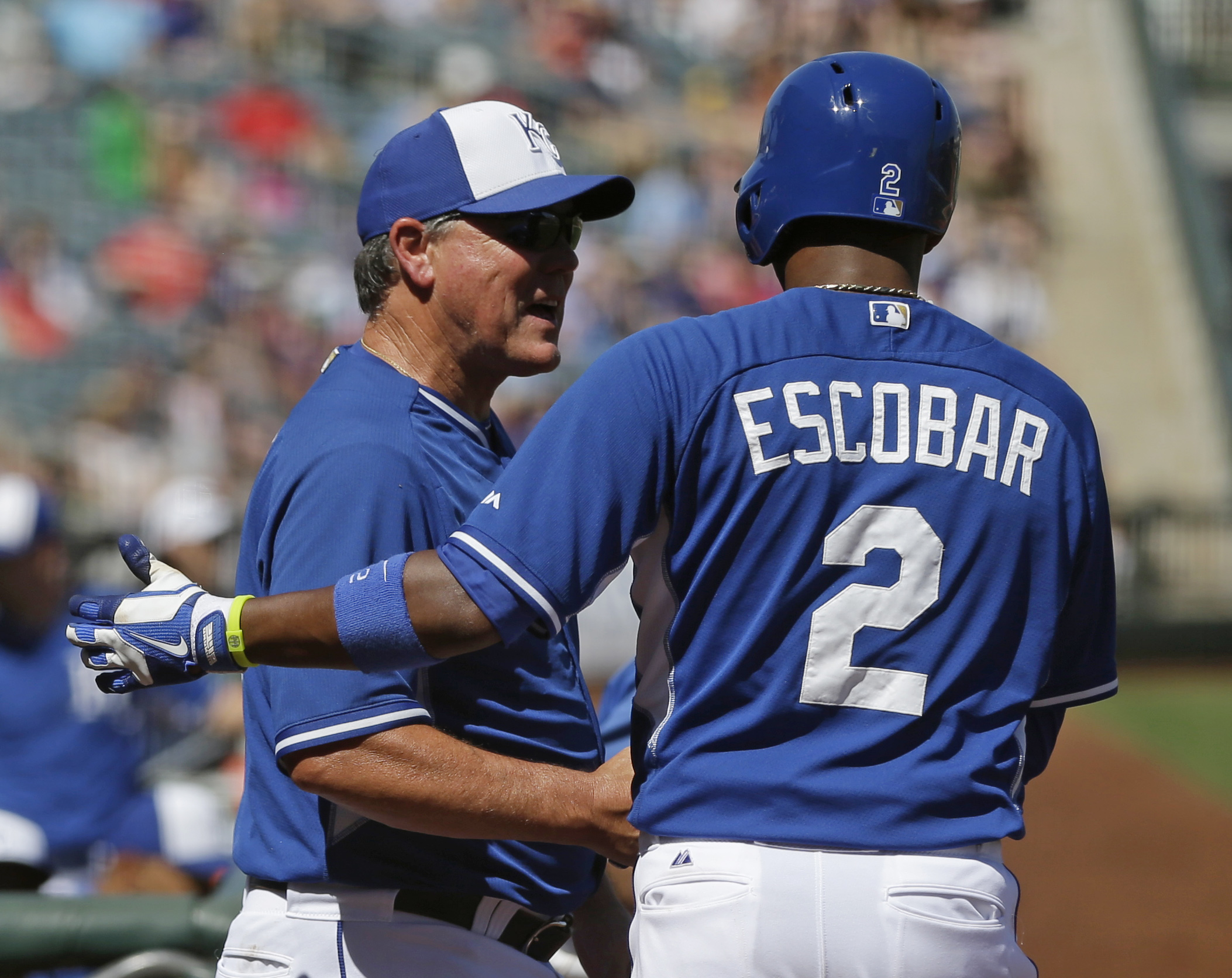 Kansas City Royals manager Ned Yost greets Alcides Escobar after he scored during the second inning of a spring exhibition baseball game against the Texas Rangers, Saturday, March 22, 2014, in Surprise, Ariz