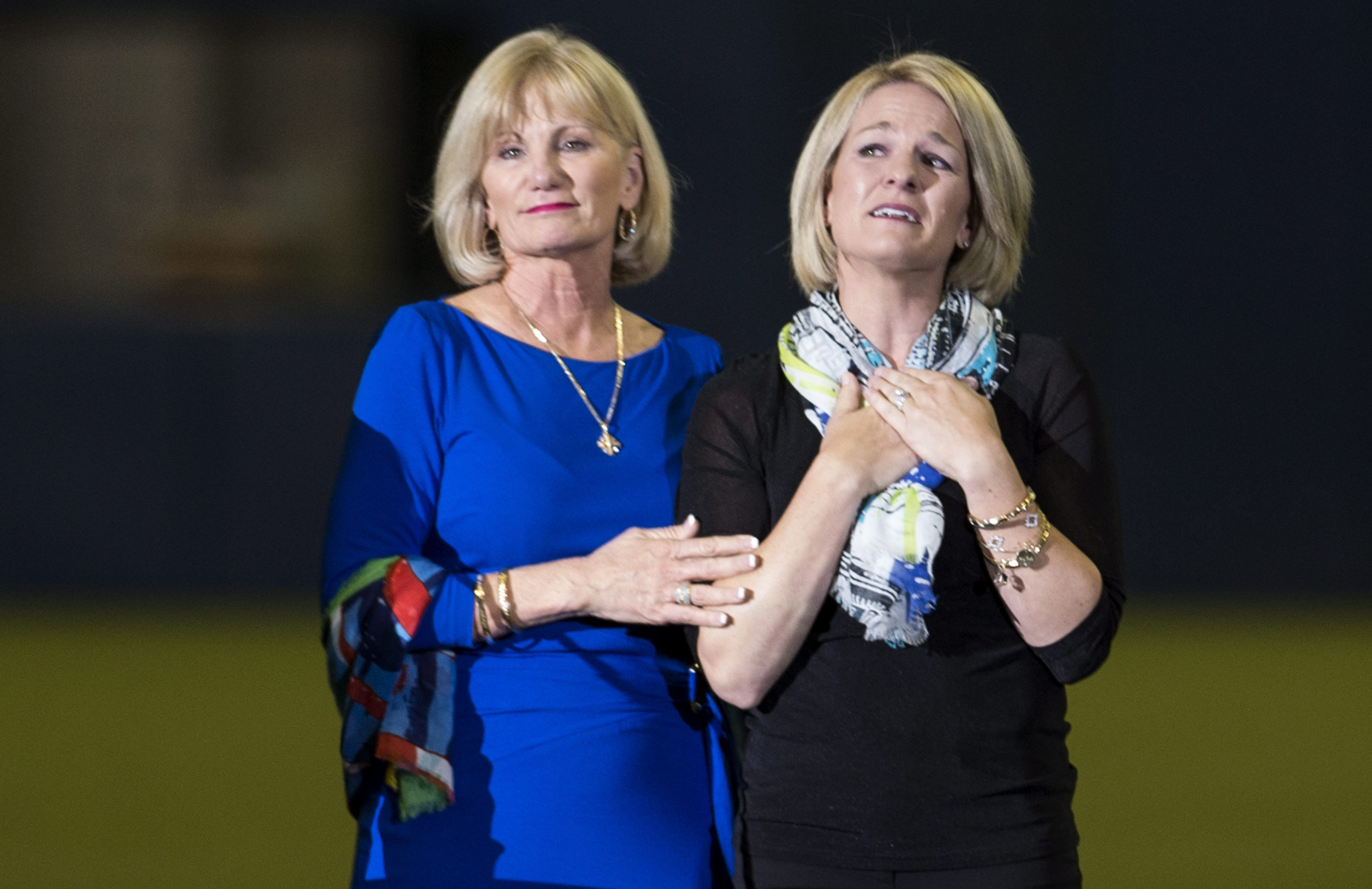 Sandy Carter, left, wife of former Montreal Expos Gary Carter, and her daughter Kimmy acknowledge applauds from the crowd during a ceremony prior to a pre-season game between the Toronto Blue Jays and the New York Mets Friday, March 28, 2014 in Montreal