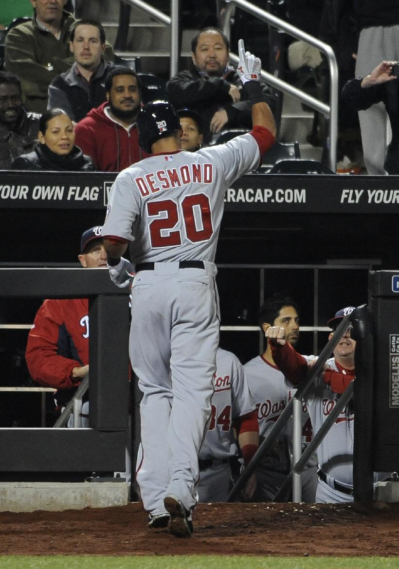 Washington Nationals' Ian Desmond (20)gestures as he is congratulated at the dugout by teammates after hitting a solo home run off New York Mets starting pitcher Bartolo Colon in the fifth inning of a baseball game at Citi Field on Wednesday, April 2, 2014, in New York