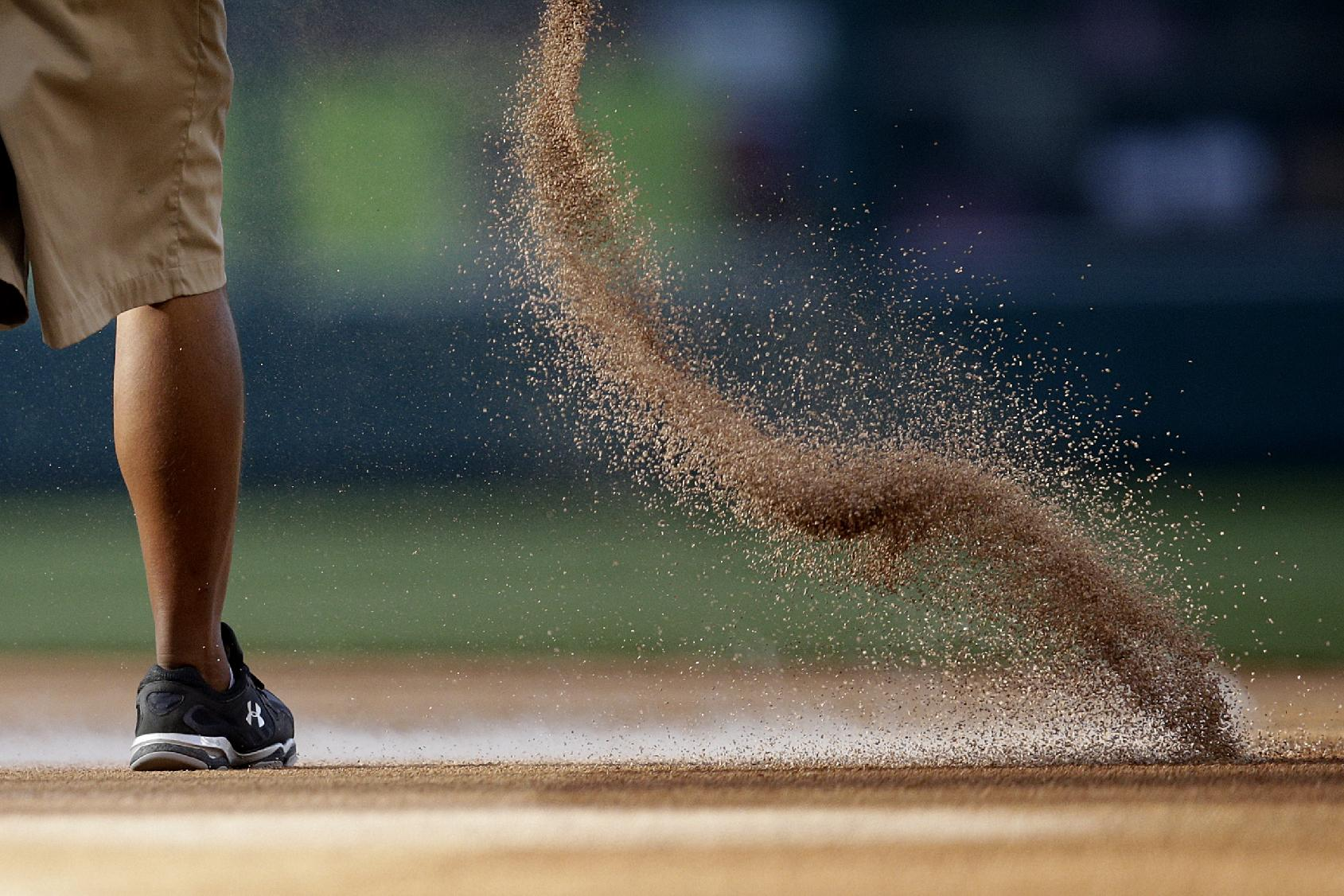 A grounds crew worker pours dirt before a baseball game between the Los Angeles Angels and the New York Mets on Saturday, April 12, 2014, in Anaheim, Calif