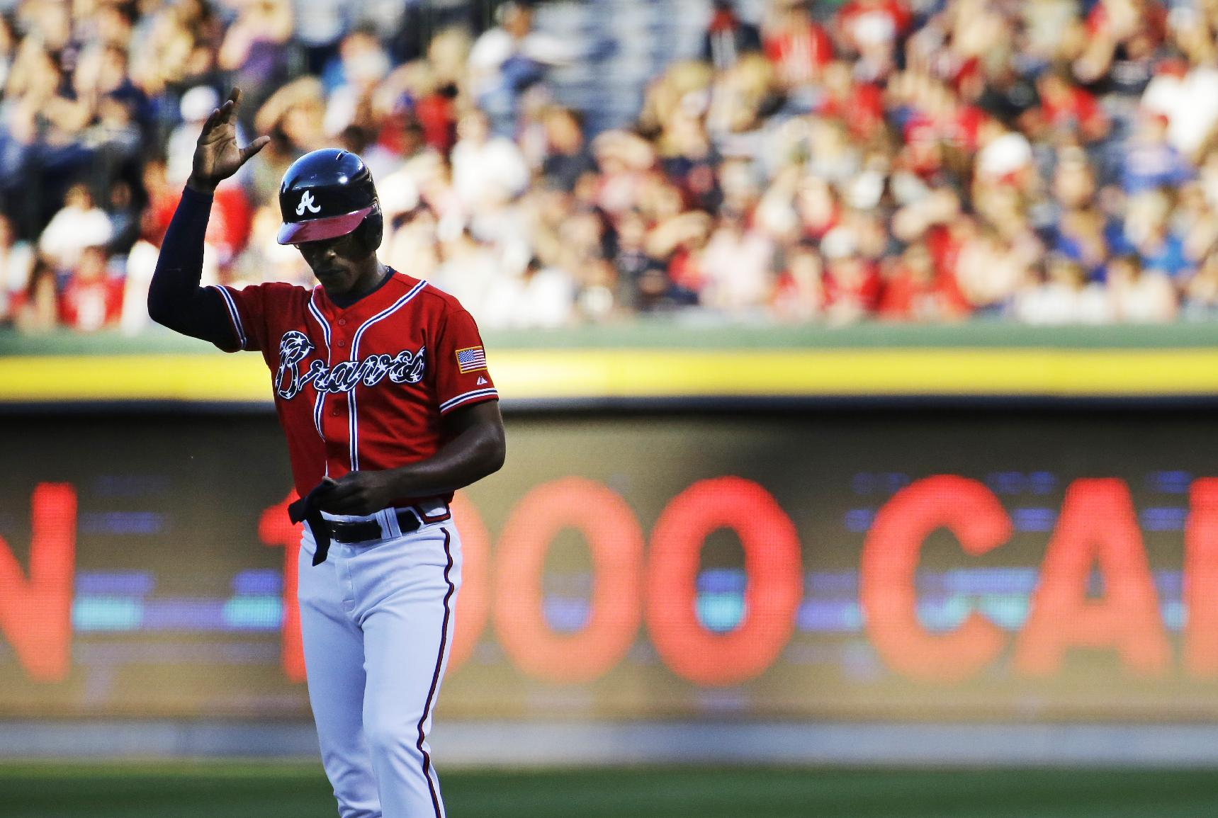 Atlanta Braves' B.J. Upton acknowledges the cheers from the crowd after hitting his 1000th career hit in the first inning of a baseball game against the Cincinnati Reds, Saturday, April 26, 2014, in Atlanta