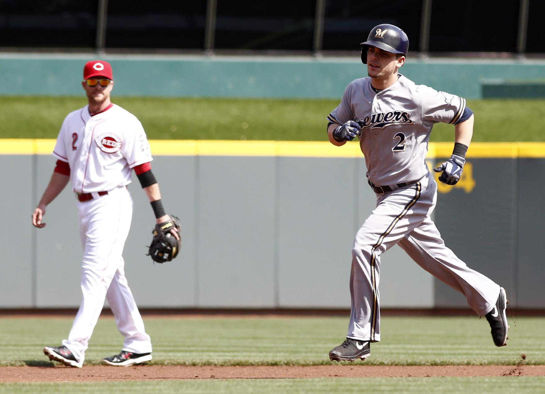 Milwaukee Brewers' Scooter Gennett, right, rounds the bases after hitting a solo home run off Cincinnati Reds starting pitcher Alfredo Simon during the first inning of a baseball game, Sunday, May 4, 2014, in Cincinnati. Reds shortstop Zack Cozart watches at left